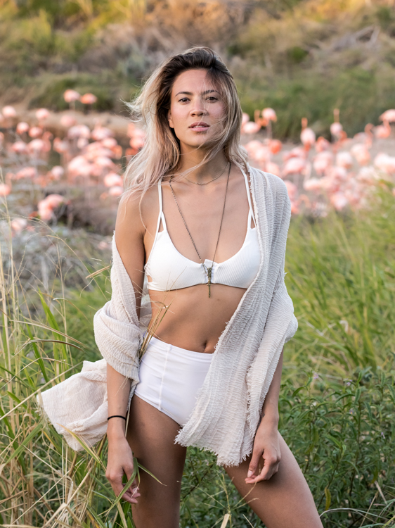 Model in a white bikini standing in the reed in front of a flamingo pond