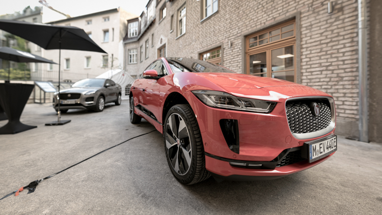 Wide-angle close-up of a red Jaguar I-Pace sportscar next to a Jaguar E-Pace in a backyard