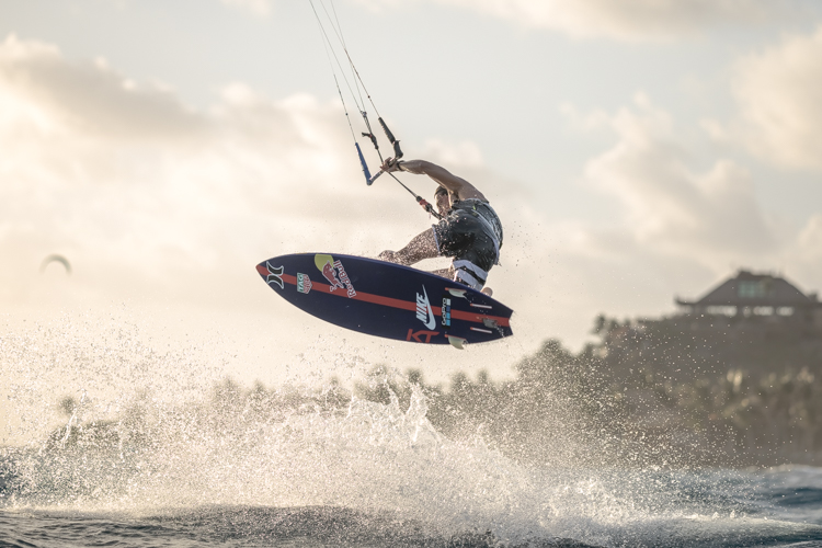 Kai Lenny kitesurfing on Necker Island doing a trick while jumping over a wave