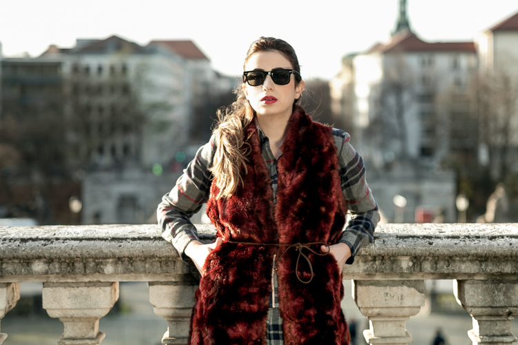 Portrait of Sara wearing sunglasses in front of the Munich skyline