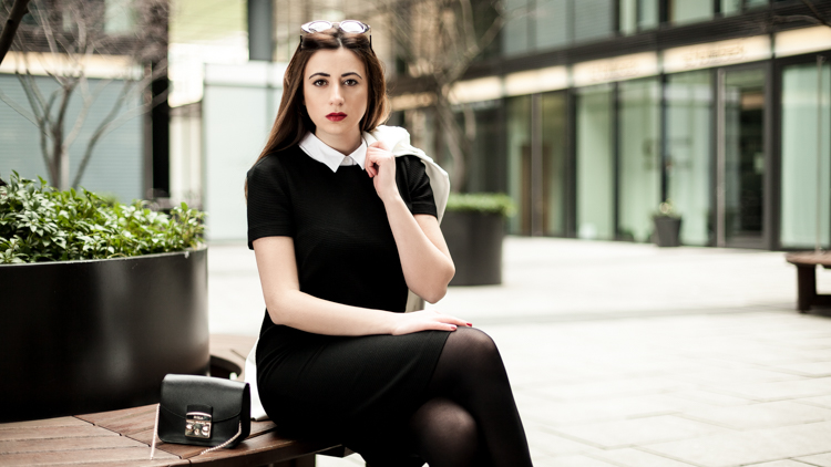 Sara in a black and white outfit sitting on a bench with a pers