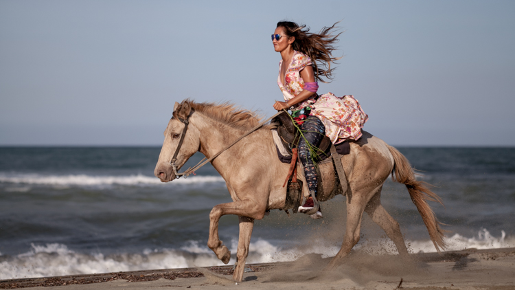 Paula Rosales in a dress riding a horse on a caribbean beach