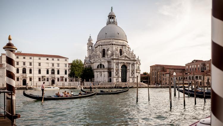 The Basilica della Santa Maria by the Gran Canal della salute in Venice with gondolas passing in the foreground.