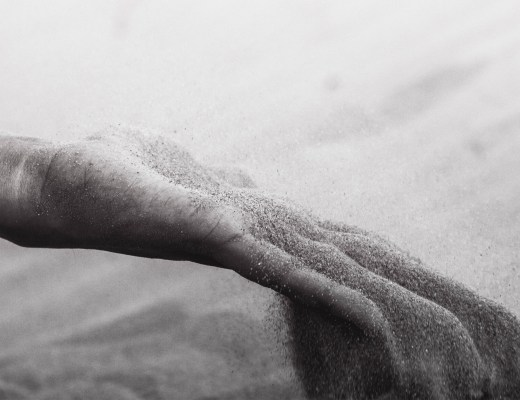 black and white photo of sand falling through fingers