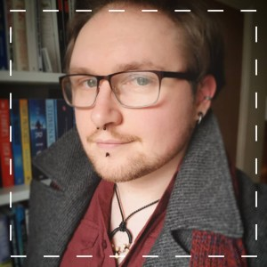 profile photo of writer matt sloan wearing grey coat and red shirt with glasses and piercings