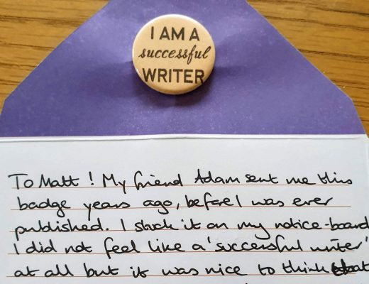 """The image shows a yellow badge reading """"I am a successful writer"""" and a letter, which reads: """"To Matt! My friend Adam sent me this badge years ago, before I was ever published. I stuck it on my notice-board. I did not feel like a 'successful writer' at all but it was nice to think that at least one person did! It also made me think about what it meant to be 'successful' at all. So now I pass it on to you! Best writing wishes! Shirley x"""""""