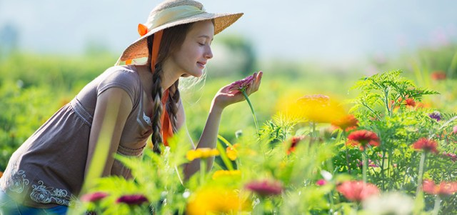 Adult woman smelling flowers and pain free