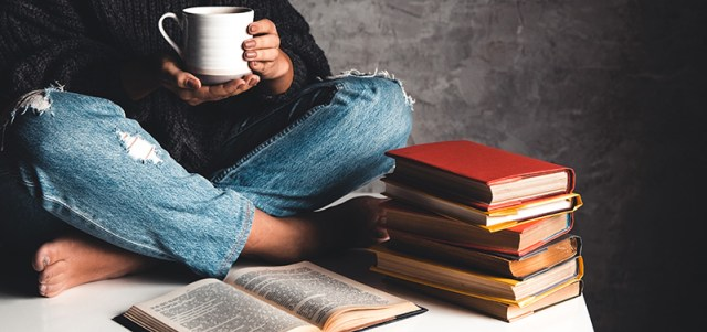 Adult person with coffee and reading books. cbd oil get you high. Can you get high from cbd?