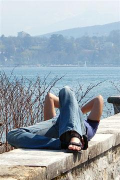 Uomo disteso su un muretto in riva al lago