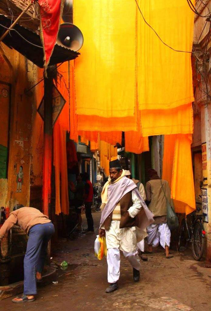 a man walks past dyed clothes in Varanasi