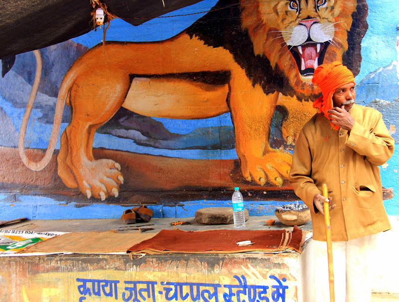 a man in front of a mural in Varanasi