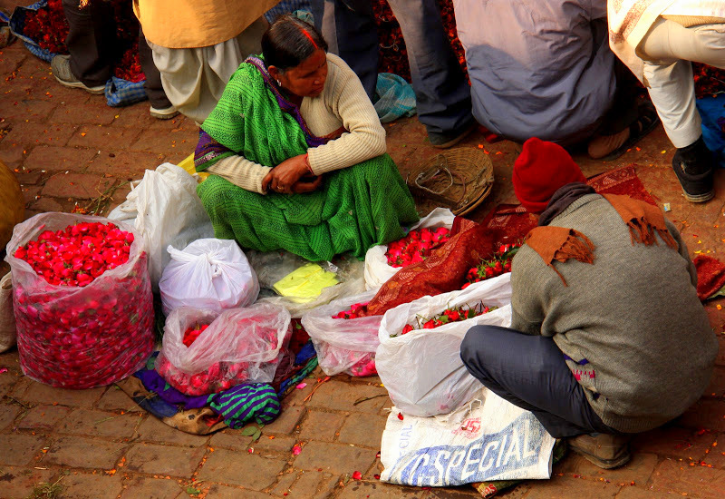 A woman selling loose petals at one of the Varanasi markets