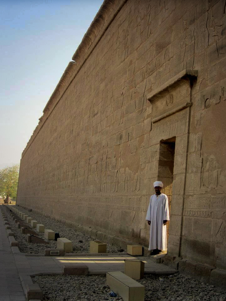 a man stands at edfu temple in upper egypt