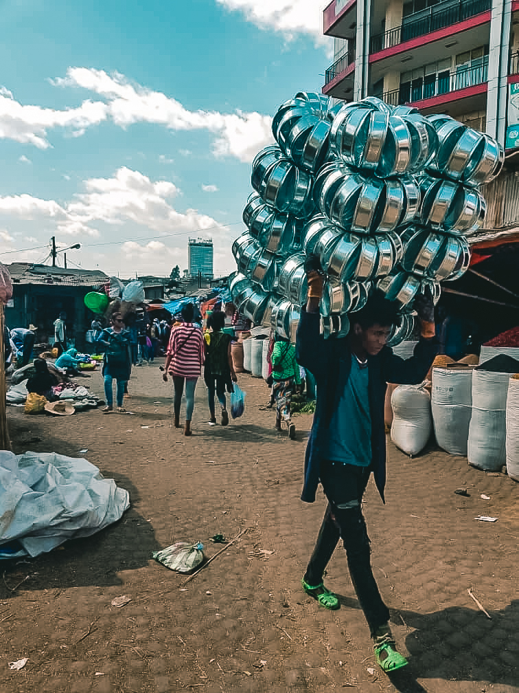 A porter carrying utensils on his head at Addis Mercato