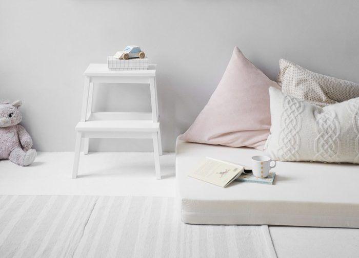 Cama montessori con colchón sobre el suelo en habitación decorada con tonos blancos