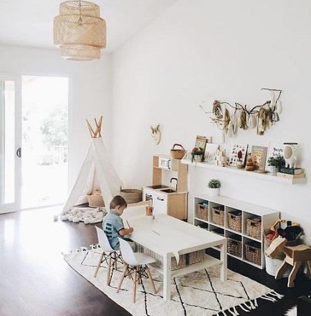 Rincón de juego montessori con mesa, alfombra y estantería baja.