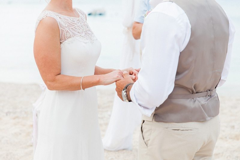 Close Up of Couple Holding Hands During Their Pastel Beach Wedding