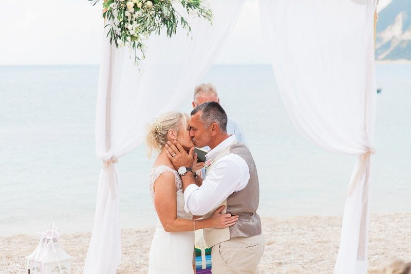 Couples First Kiss During Their Pastel Beach Wedding
