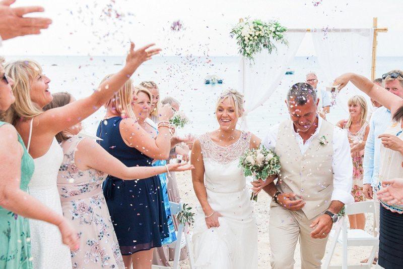 Couple Walking Through Confetti During Their Pastel Beach Wedding