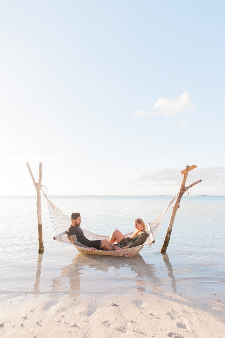 Couple in a hammock at sunset during their Mauritius engagement session