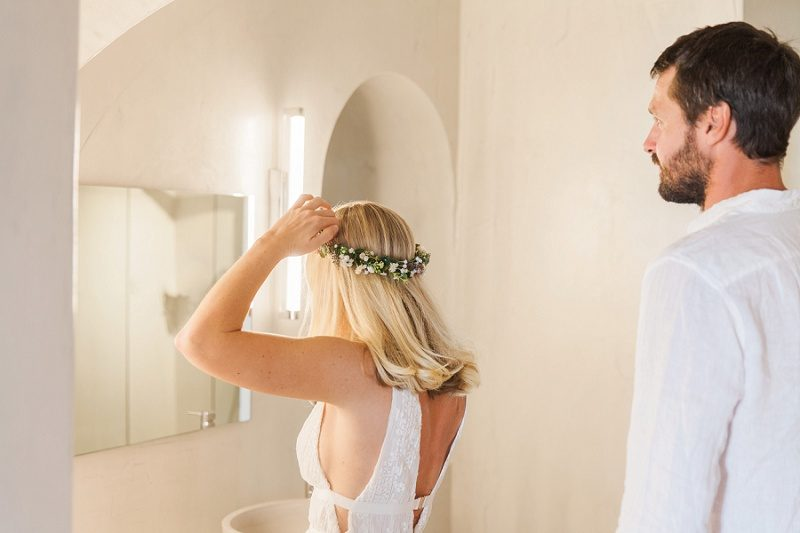 Bride Putting On Flower Crown in the Bridal Suite at Mystical Blue in Santorini