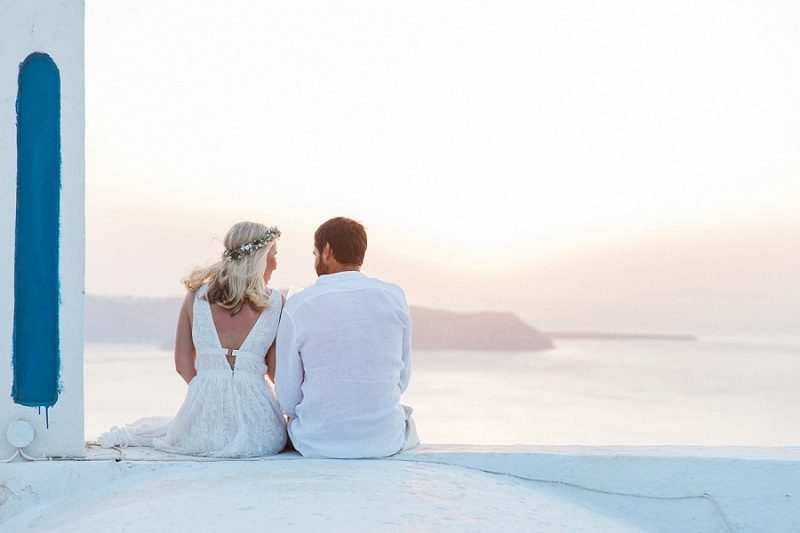 Couple On A Church Rooftop After Their Sunset Elopement in Santorini