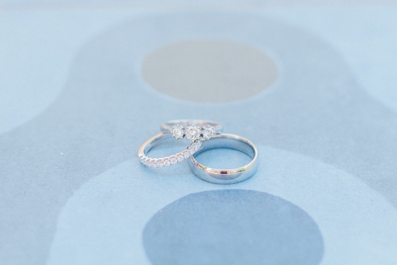 Brides three stone diamond engagment ring, eternity band and the grooms ring on blue tiles