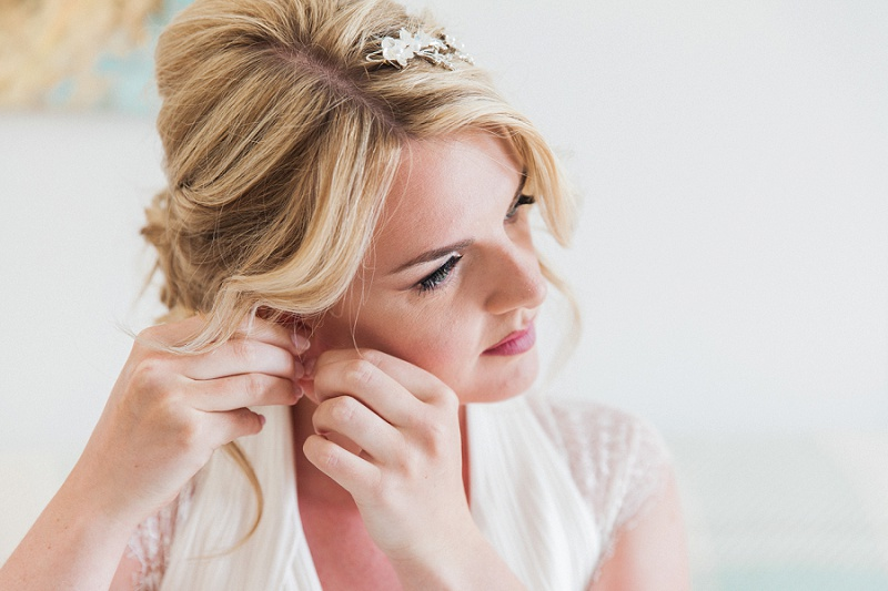 Close up of the bride putting in her crystal earrings