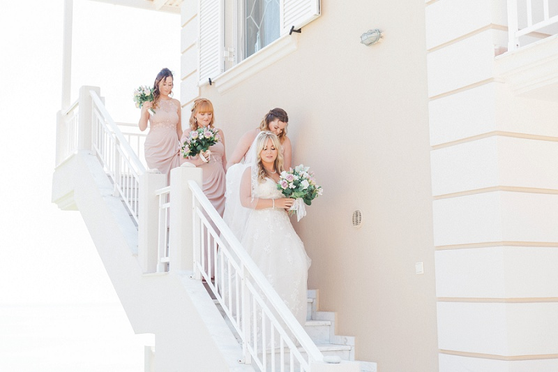 Bride and Bridesmaids making their way down the stairs of their villa to meet her father.