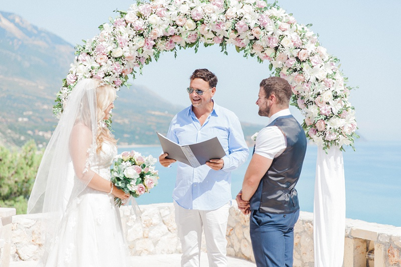 Bride and Groom exchanging vows under a pink and white floral arch with a view of the sea.