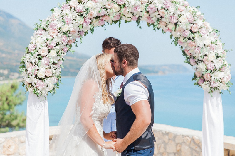 Bride and Groom share their first kiss under a floral arch at their villa wedding on Kefalonia