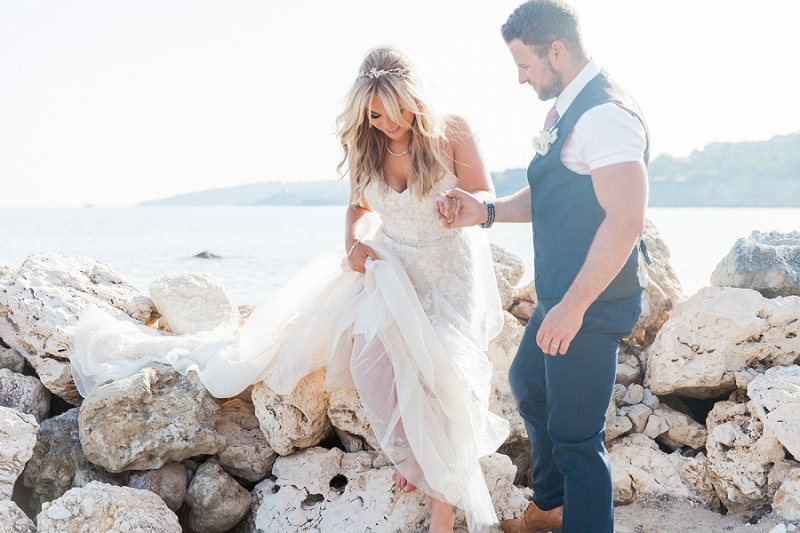Groom helping the bride off the rocks on a Kefalonian beach
