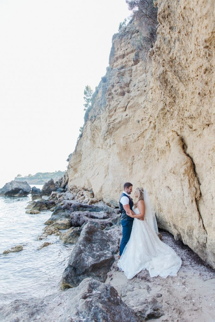 Bride and groom on the beach embracing against a backdrop of dramatic Kefalonian coastline