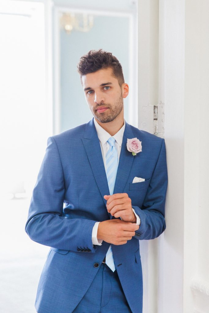 Portrait of the groom in a blue suit on the morning of his wedding at 10-11 Carlton House Terrace in London