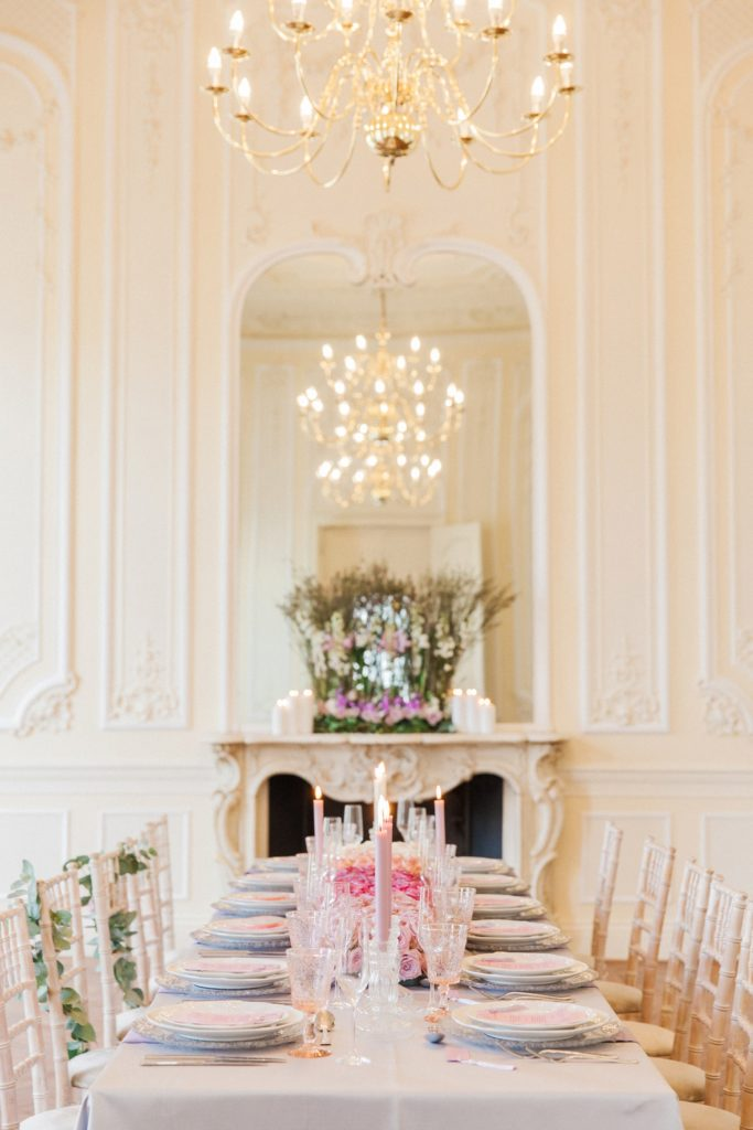 Tablescape featuring a decorated fireplace, chandelier and pink ombre wedding table runner at 10-11 Carlton House Terrace in London