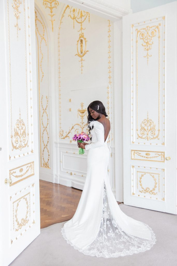 Black bride poses with a purple dahlia and cala lily and coral rose bouquet at her 10-11 Carlton House Terrace wedding