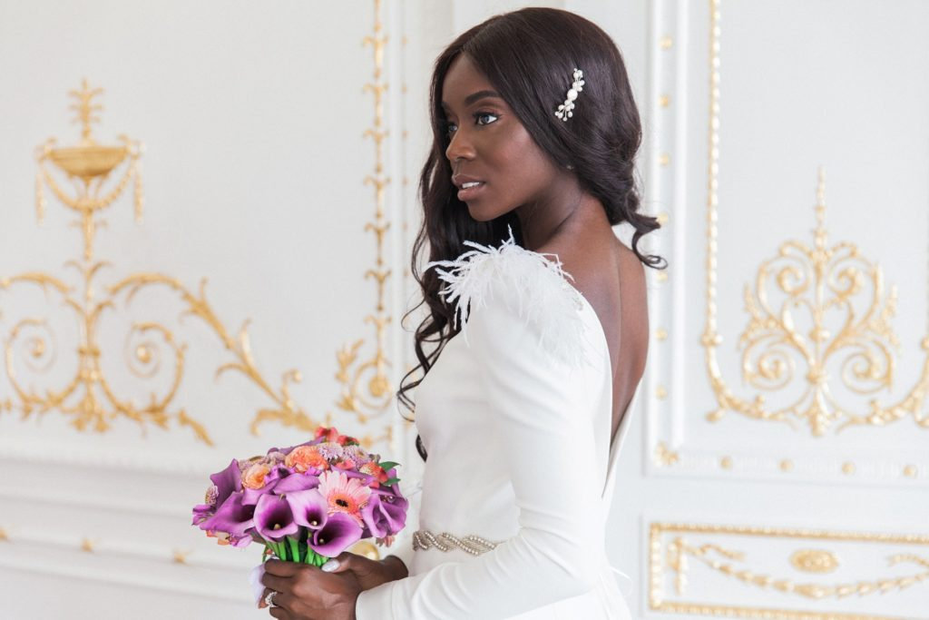 Black bride standing in the ornate doorway of 10-11 Carlton House Terrace on the day of her wedding in London