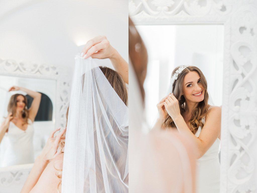 The bride puts on her veil before her Santorini elopement