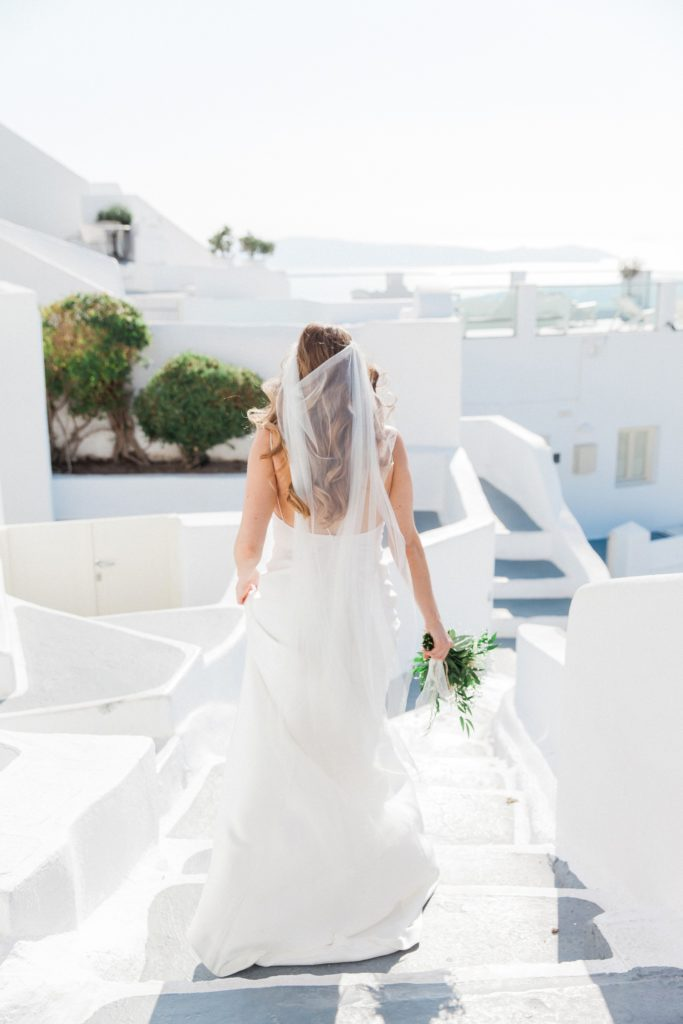 Bride makes her way down the stairs to her elopement ceremony at Dana Villas Santorini