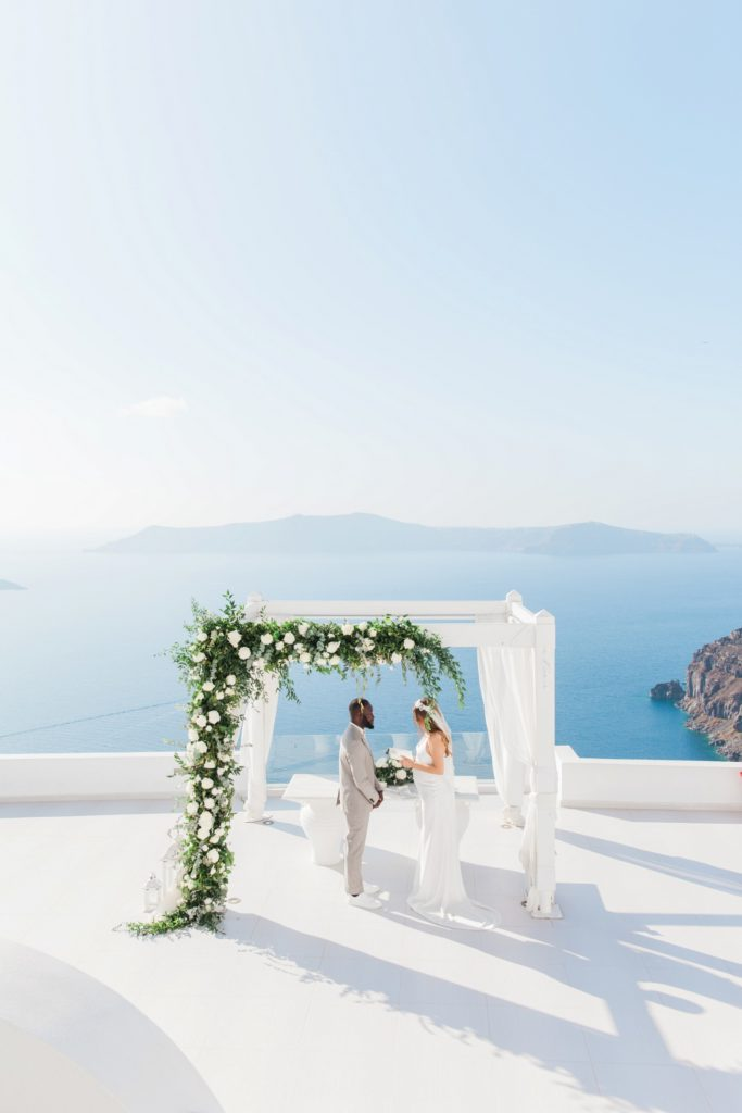 Bride and groom under their wedding arch with a view over the caldera at Dana Villas Santorini
