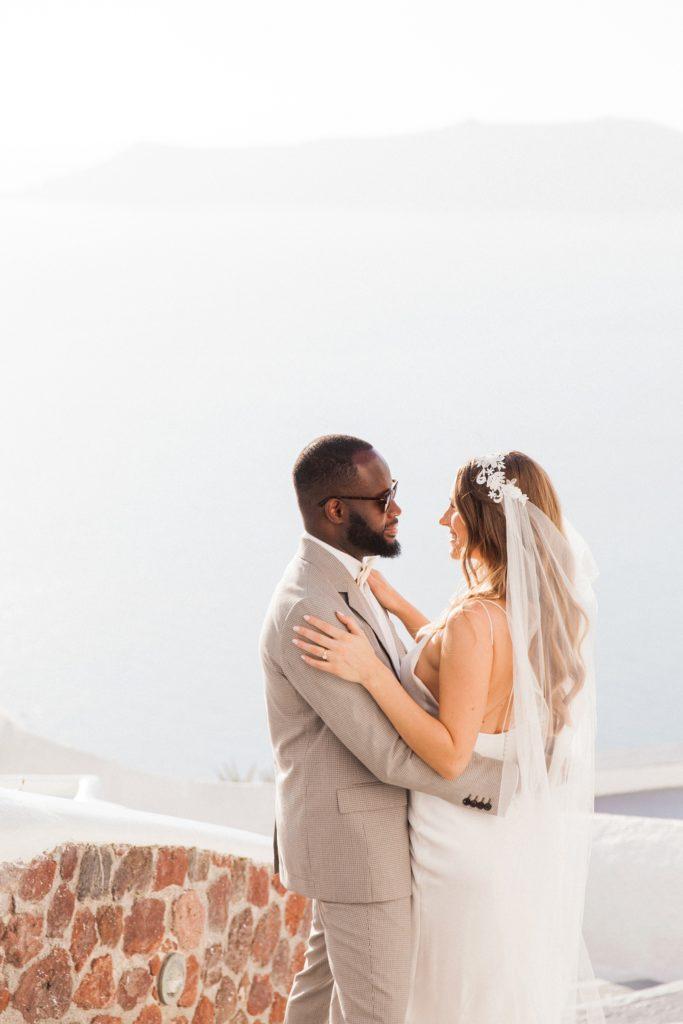 Bride and groom in Santorini against a veiw of the caldera
