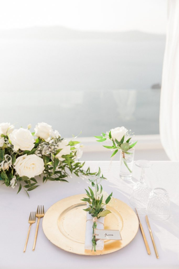 White and gold elopement table setting with a view across the caldera in Santorini
