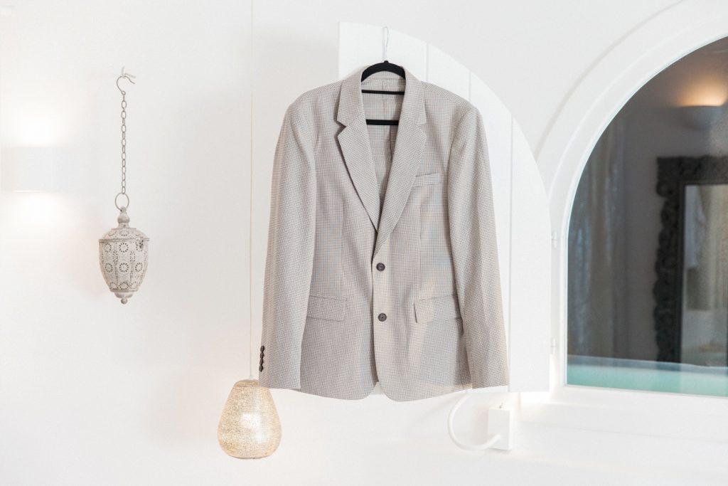 Grooms Sandro suit handing in the suite at Dana Villas in Santorini