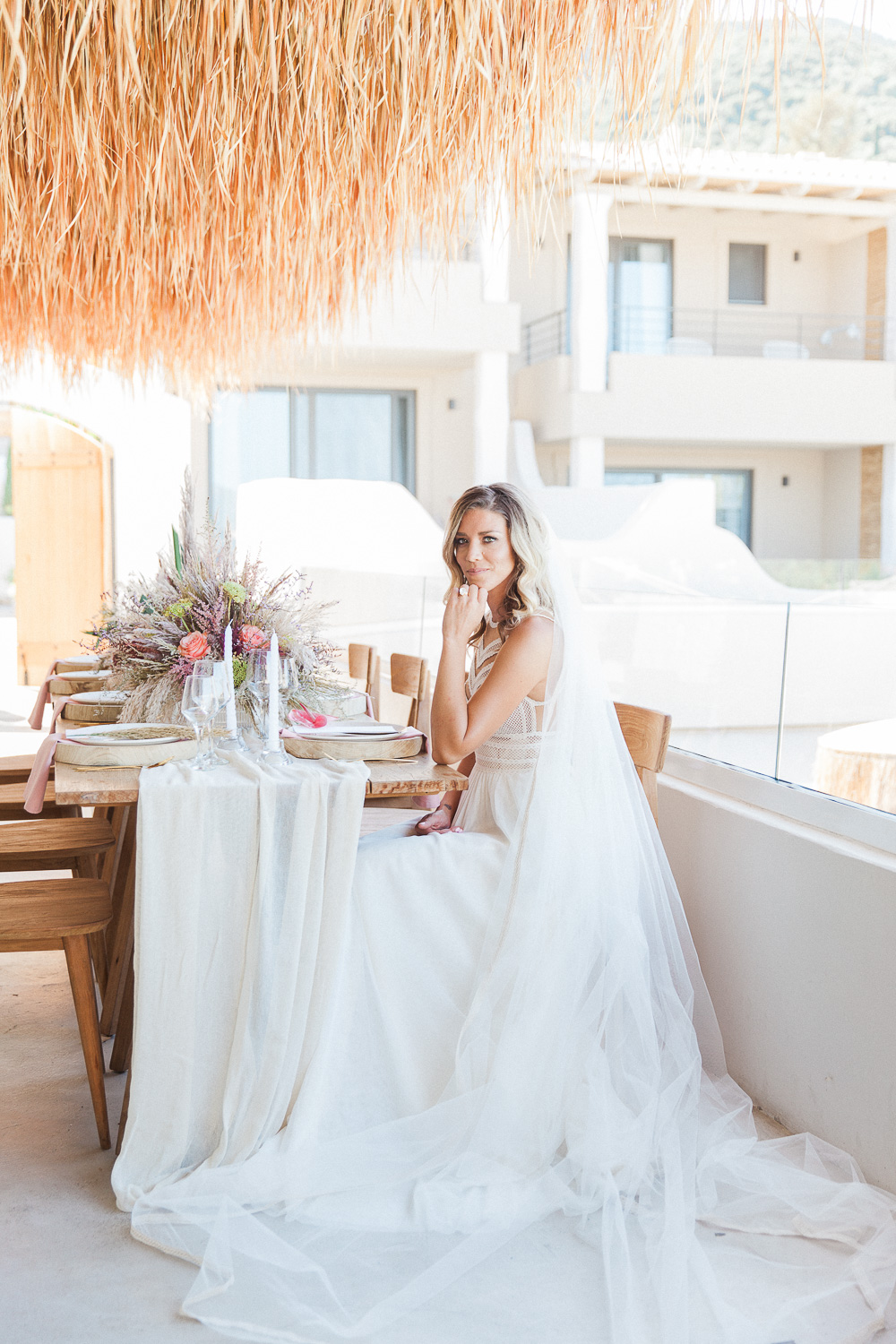 Bride wearing an Atelier Zolotas gown seated at her boho wedding table at Crystal Waters Lefkada in Greece