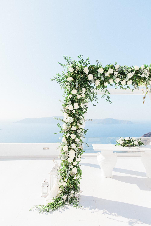 White rose and greenery wedding arch at Dana Villas Santorini wedding