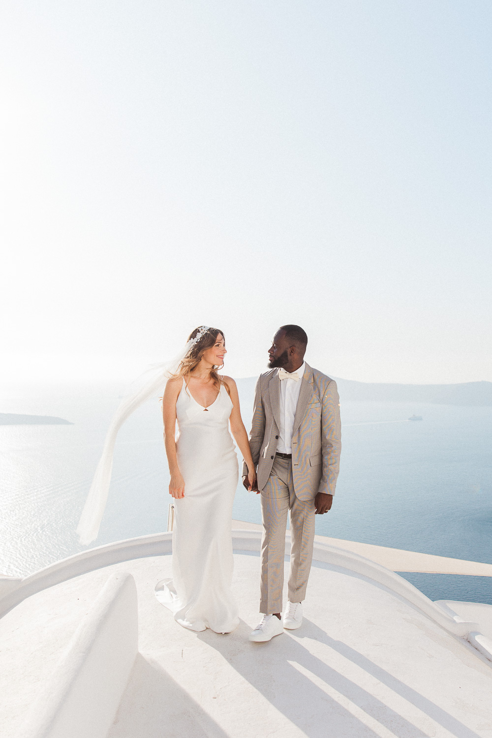 Bride and groom walking on a Santorini rooftop on their wedding day