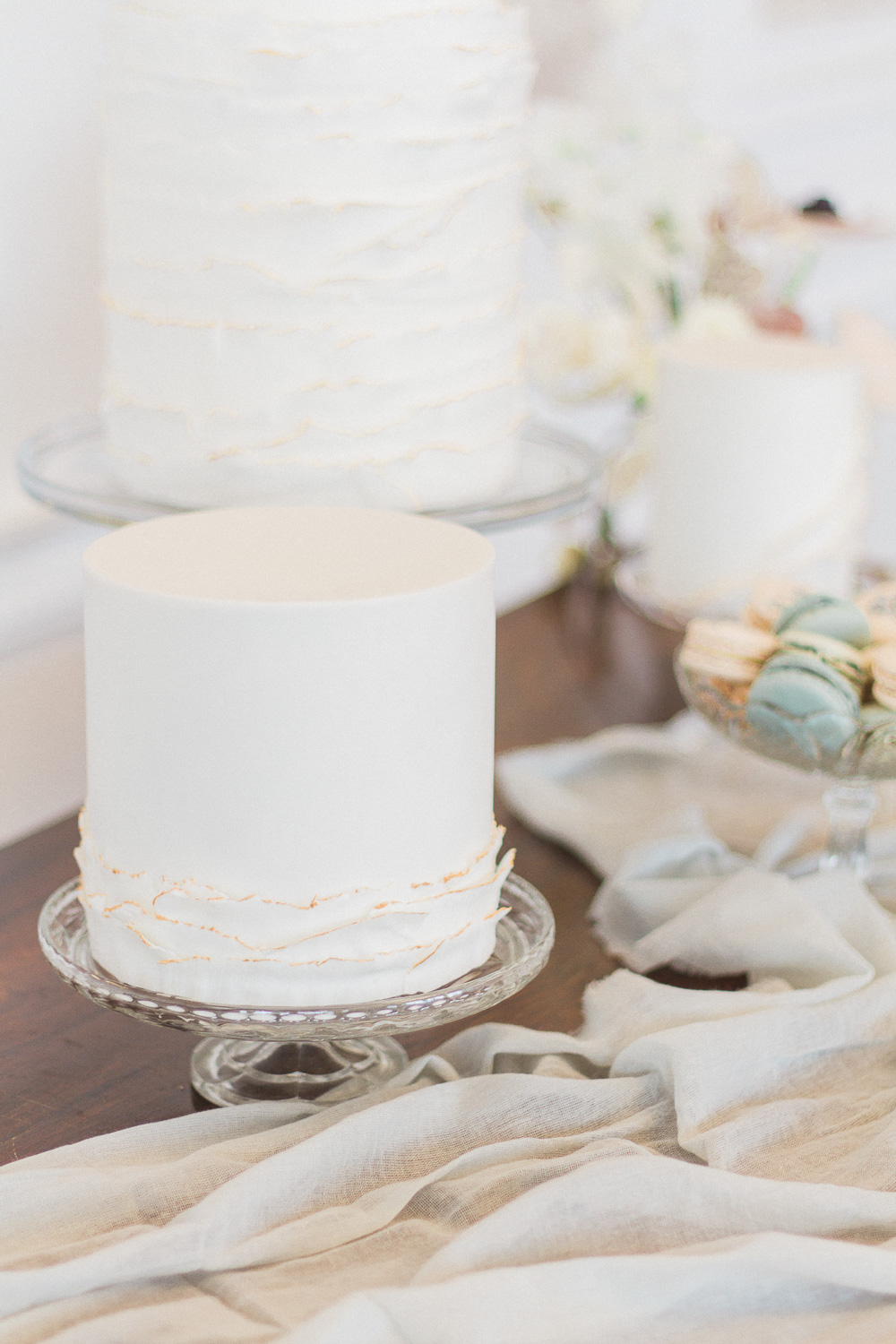 Dessert table with white cakes with gold edging by Anna Lewis at Froyle Park wedding venue in the UK