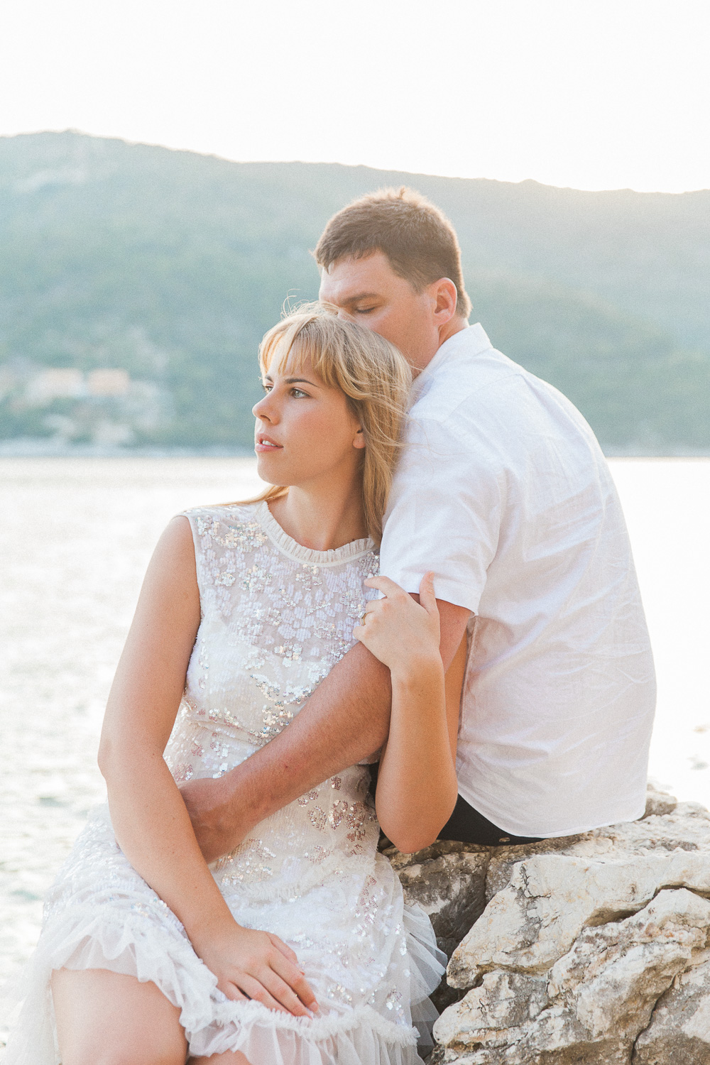 Bride and groom sitting on rocks at their Lefkada wedding