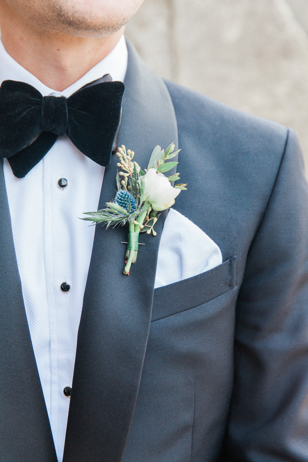 Image of a grooms black bowtie and buttonhole by London wedding photographer Maxeen Kim