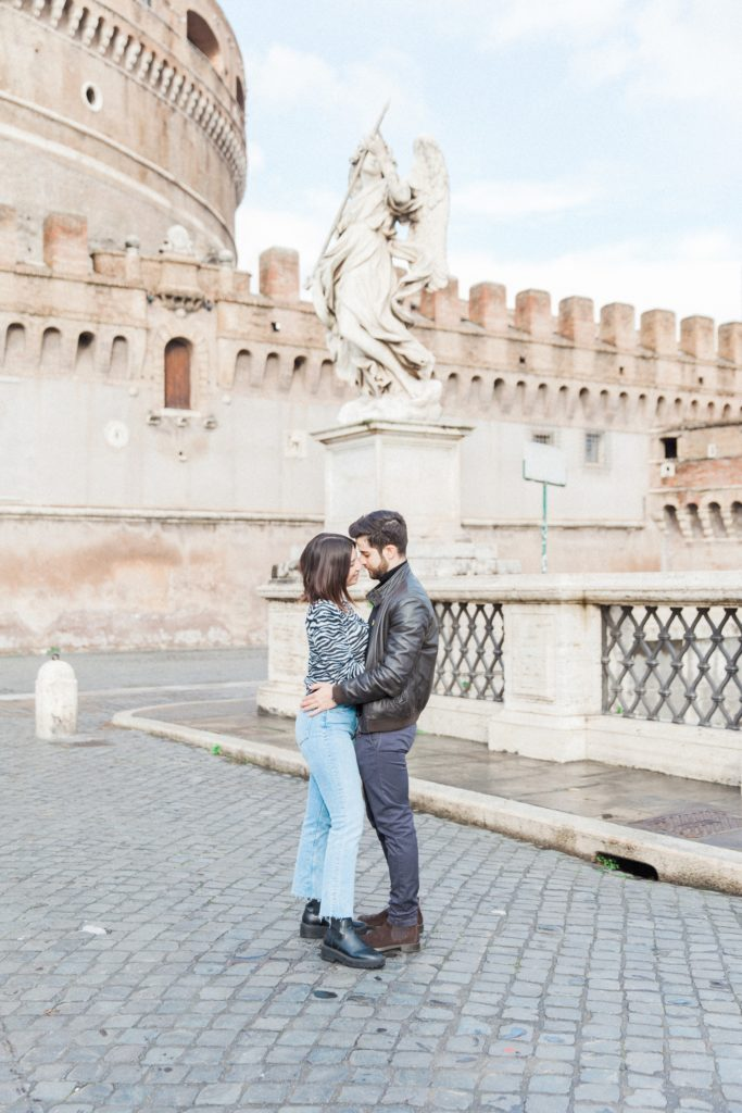 Couple kiss on the bridge in front of Castel Sant'Angelo in Rome, Italy